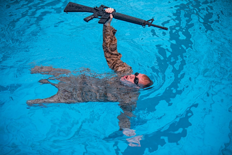 Navy Petty Officer 2nd Class Christopher Walters, a hospital corpsman with 3rd Medical Battalion, 3rd Marine Logistics Group, conducts a rifle swim during the water survival advanced course on Marine Corps Air Station Futenma, Okinawa, Japan, June 17, 2021. WSA is the highest swim qualification Marines and sailors can obtain before moving onto the next echelon of becoming a Marine Corps Instructor of Water Survival. The week-long course kicks off with a water survival pre screening event, and the remainder of the course consists of numerous endurance swims, life-saving techniques and applications, physical and mental conditioning, and countless swimming drills to ensure students have the confidence to not only maintain themselves but others' lives while in the water. Walters is a native of Upland, California.