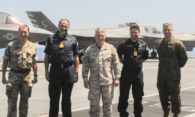 SICILY, Italy–  Gen. Kenneth McKenzie, commander, U.S. Central Command, center, poses for a photo with United Kingdom Carrier Strike Group leaders aboard HMS Queen Elizabeth June 14, 2021. Gen. McKenzie boarded the British Royal Navy ship from the Port of Augusta, the first in a series of port visits en route to the Mediterranean for the HMS Queen Elizabeth's first operational deployment. The aircraft carrier launches F-35B Joint Strike Fighters operated and maintained by U.S. and British servicemembers.