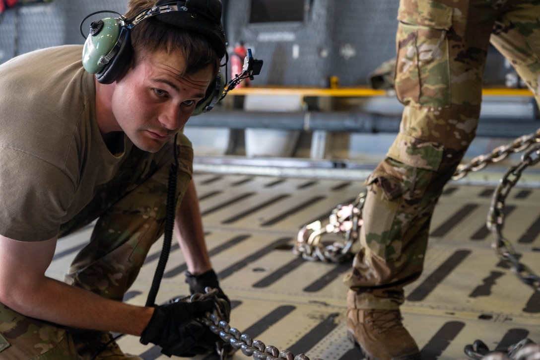 Staff Sgt. John Dittess, 9th Airlift Squadron loadmaster, chains a K-loader to the cargo compartment of a Dover Air Force Base C-5M Super Galaxy during a Major Command Service Tail Trainer at Holloman AFB, June 9, 2021. Loadmasters from the 9th AS coordinated cargo with Airmen from Air Education and Training Command's 49th Wing and Air Force Materiel Command's 635th Materiel Maintenance Group to complete the 10-day MSTT. Over the course of the training, Airmen loaded and unloaded 320,085 pounds of cargo, including palletized cargo, aircraft ground equipment, a fuel truck and a K-loader. (U.S. Air Force photo by Senior Airman Faith Schaefer)