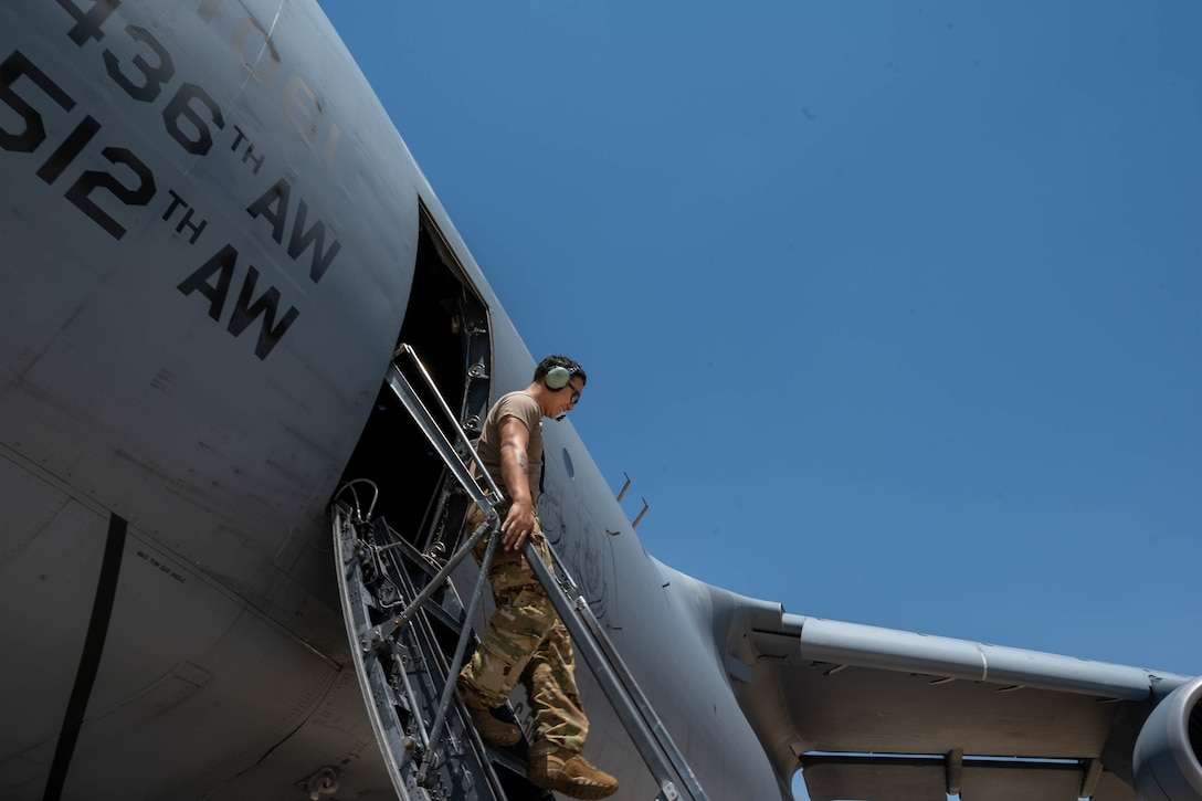 Staff Sgt. Alex Delamarter, 9th Airlift Squadron flight engineer student, climbs down the crew stairs of a Dover Air Force Base C-5M Super Galaxy during a Major Command Service Tail Trainer at Holloman AFB, New Mexico, June 7, 2021. The 9th AS performs MSTTs to expedite upgrade and qualification training for C-5M loadmasters and flight engineers. This MSTT was coordinated in partnership with Air Education Training Command's 49th Wing and Air Force Materiel Command's 635th Materiel Maintenance Group. (U.S. Air Force photo by Senior Airman Faith Schaefer)