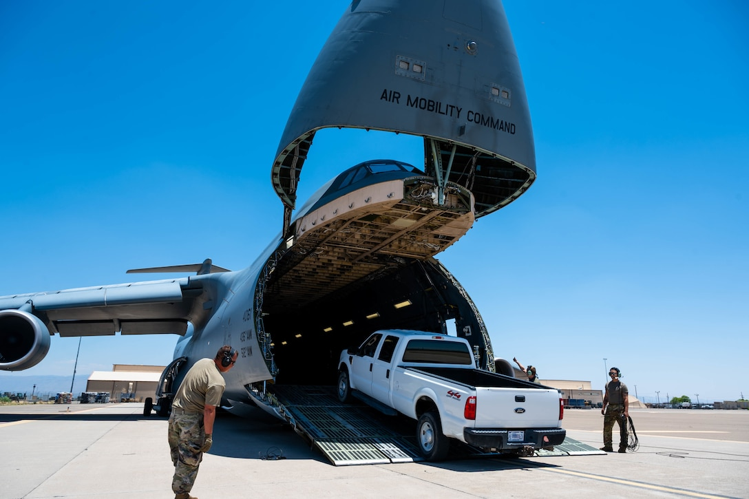 A truck is loaded onto a Dover Air Force Base C-5M Super Galaxy during a Major Command Service Tail Trainer at Holloman AFB, New Mexico, June 7, 2021. The 9th AS performs MSTTs to expedite upgrade and qualification training for C-5M loadmasters and flight engineers. This MSTT was coordinated in partnership with Air Education Training Command's 49th Wing and Air Force Materiel Command's 635th Materiel Maintenance Group. (U.S. Air Force photo by Senior Airman Faith Schaefer)