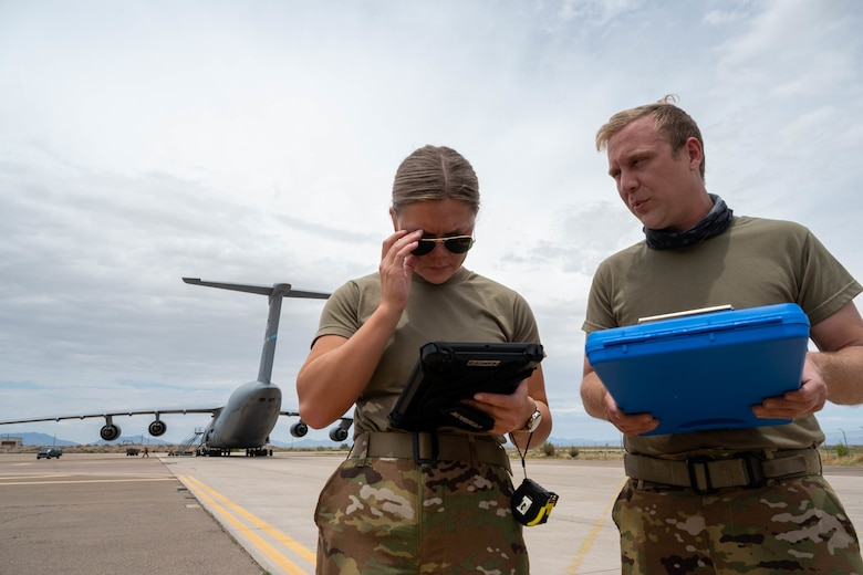 Airman 1st Class Rebecca Reimer, left, 9th Airlift Squadron student loadmaster, and Staff Sgt. Justin Thomas, 9th AS noncommissioned officer in charge of loadmaster training, discuss a joint inspection checklist during a Major Command Service Tail Trainer at Holloman Air Force Base, New Mexico, June 2, 2021. The 9th AS performs MSTTs to expedite upgrade and qualification training for C-5M loadmasters and flight engineers. Of the 350 tasks needed to be a fully qualified loadmaster, roughly half can be completed during an MSTT,  reducing training time by up to 35 days. (U.S. Air Force photo by Senior Airman Faith Schaefer)