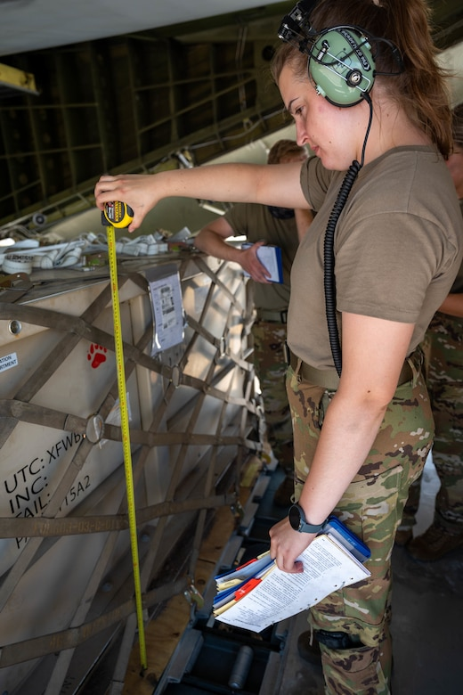 Senior Airman Amelia Bradfield, 9th Airlift Squadron loadmaster, measures the height of a cargo box before loading it onto a Dover Air Force Base C-5M Super Galaxy during a Major Command Service Tail Trainer exercise at Holloman AFB, New Mexico, June 2, 2021. The 9th AS performs MSTTs to expedite upgrade and qualification training for C-5M loadmasters and flight engineers. Over the course of the 10-day MSTT, 9th AS loadmasters loaded and unloaded 320,085 pounds of cargo, including palletized cargo, aircraft ground equipment, a fuel truck and a K-loader. (U.S. Air Force photo by Senior Airman Faith Schaefer)