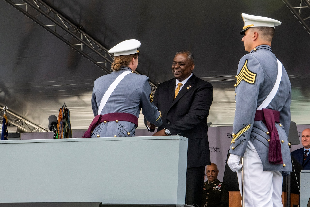 Secretary of Defense Lloyd J. Austin III smiles and shakes hands with a U.S. Military Academy cadet on an outdoor podium.