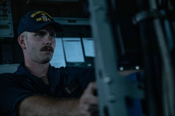 Gunner's Mate 3rd Class David Feder, from Conroe, Texas, stands watch aboard Arleigh Burke-class guided-missile destroyer USS Curtis Wilbur (DDG 54) as the ship conducts routine operations.