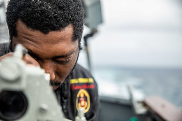 Culinary Specialist 3rd Class Curtis Lynch, from Petersburg, Va., stands watch on the bridge wing of Arleigh Burke-class guided-missile destroyer USS Curtis Wilbur (DDG 54) as the ship conducts routine operations.