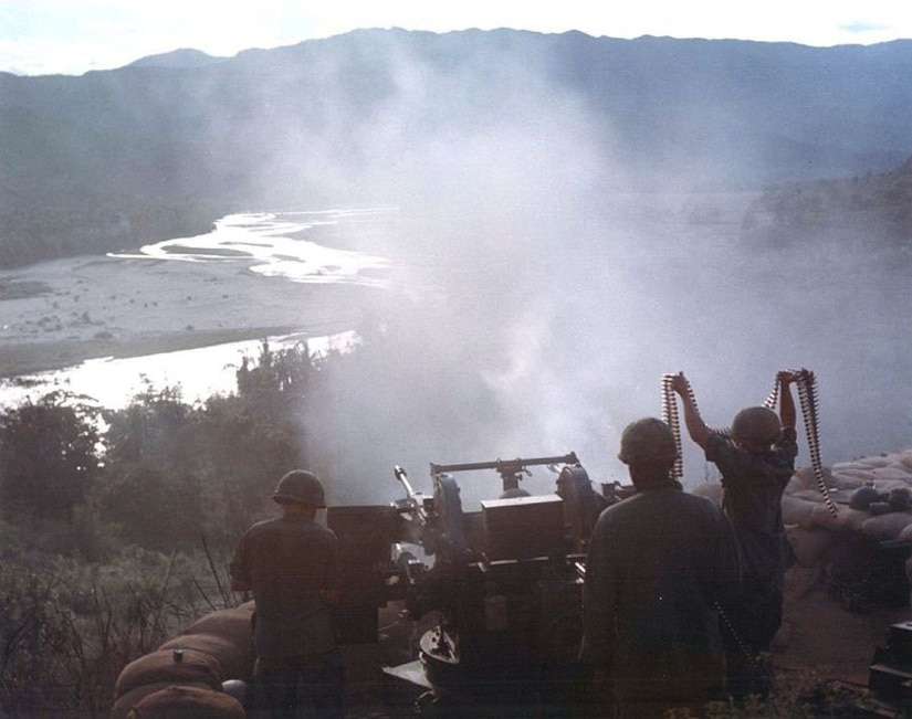 A soldier holds a string of ammunition above his head as two other soldiers work to shoot a large machine gun into a valley.