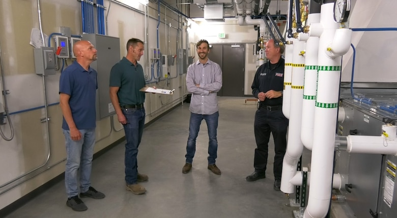 Members from the USACE, Omaha District's Fort Carson South office (from left) Dan Morak, Justin Scherzberg, Ken Hombostel, and Fort Carson fire inspector,Rob Wurchner,check a mechanical room during a post-construction walk through May 19.