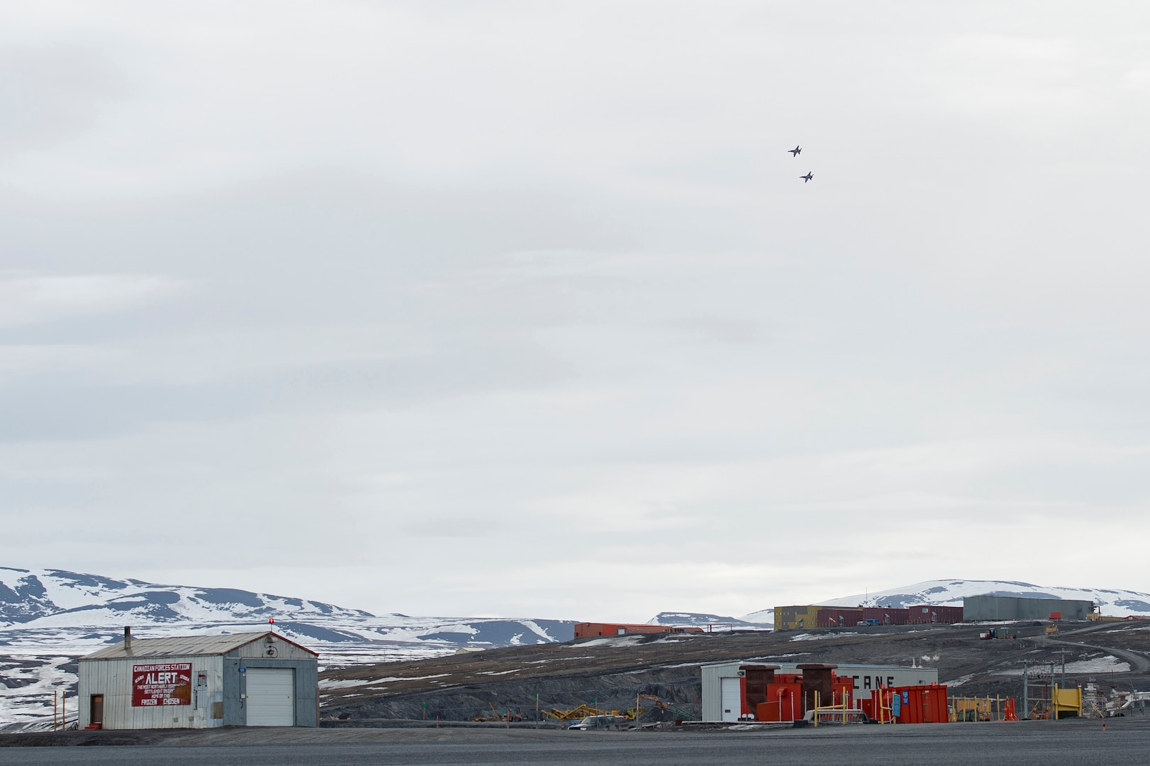 Two jets fly over an Arctic air field.