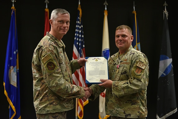 U.S. Air Force Col. Tony England, 17th Mission Support Group commander, presents Lt. Col. Richard Buckley, outgoing 17th Security Forces Squadron commander, the Meritorious Service Medal during the change of command ceremony at the Event Center on Goodfellow Air Force Base, Texas, June 22, 2021. Buckley was decorated for his performance and leadership of the 17th SFS, which led to numerous annual awards and a Major Command Award. (U.S. Air Force photo by Senior Airman Ashley Thrash)