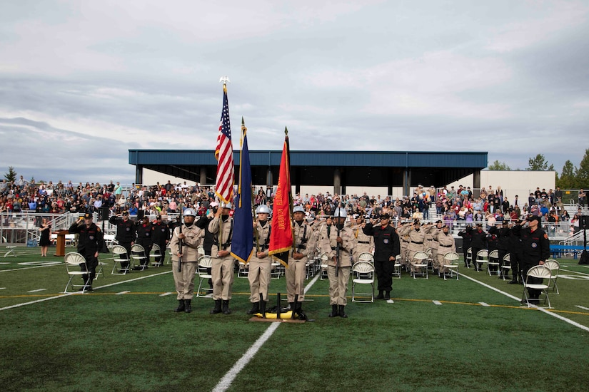The Alaska Military Youth Academy color guard team presents the colors while the national anthem plays during AMYA's graduation ceremony, held at the Bartlett High School Football Field in Anchorage, June 18, 2021. The ceremony featured Alaska Lt. Gov. Kevin Meyer as the keynote speaker for the 79 graduating cadets and their families. (U.S Army National Guard photo by Victoria Granado)