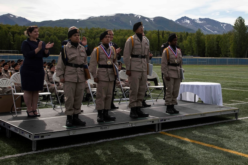 Alaska Military Youth Academy cadets stand for applause after receiving awards at AMYA's graduation ceremony, held at the Bartlett High School Football Field in Anchorage, June 18, 2021. The ceremony featured Alaska Lt. Gov. Kevin Meyer as the keynote speaker for the 79 graduating cadets and their families. (U.S Army National Guard photo by Victoria Granado)