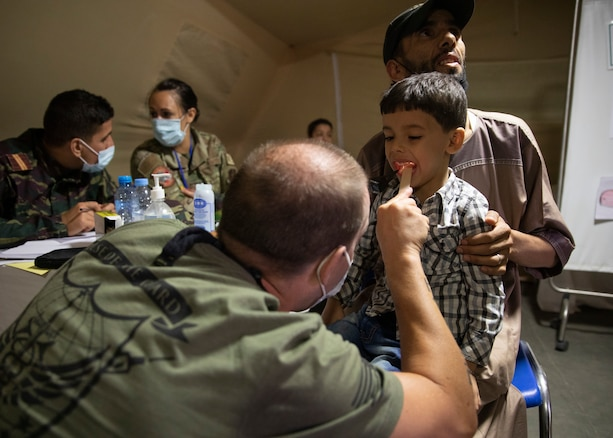 A U.S. military physician assistant inserts a medical instrument into the ear of a Moroccan boy while the boys father looks on.