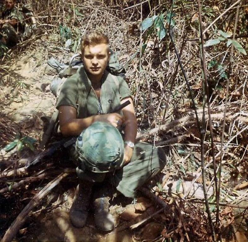 A soldier kneels in jungle terrain.