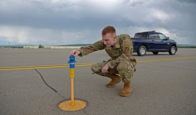 U.S. Air Force Senior Airman Zachary Rodgers, 354th Operations Support Squadron Airfield Management Flight shift lead, inspects an airfield light during RED FLAG-Alaska 21-2 on Eielson Air Force Base, Alaska, June 21, 2021. Rodgers' responsibilities include checking the airfield for debris, damage, and wildlife, and ensuring all runway lights are functioning. (U.S. Air Force photo by Senior Airman Beaux Hebert)