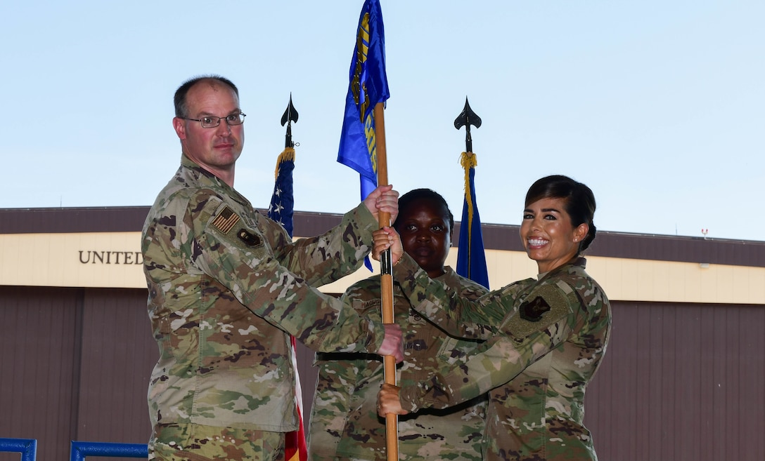 During the ceremony, Col. Mark Reynolds, 509th Medical Group commander, passed the unit flag to Lt. Col. Jessica Dees as a symbol of the continuity of authority between the outgoing and incoming commanders. (U.S. Air Force photo by Tech. Sgt. Heather Salazar)