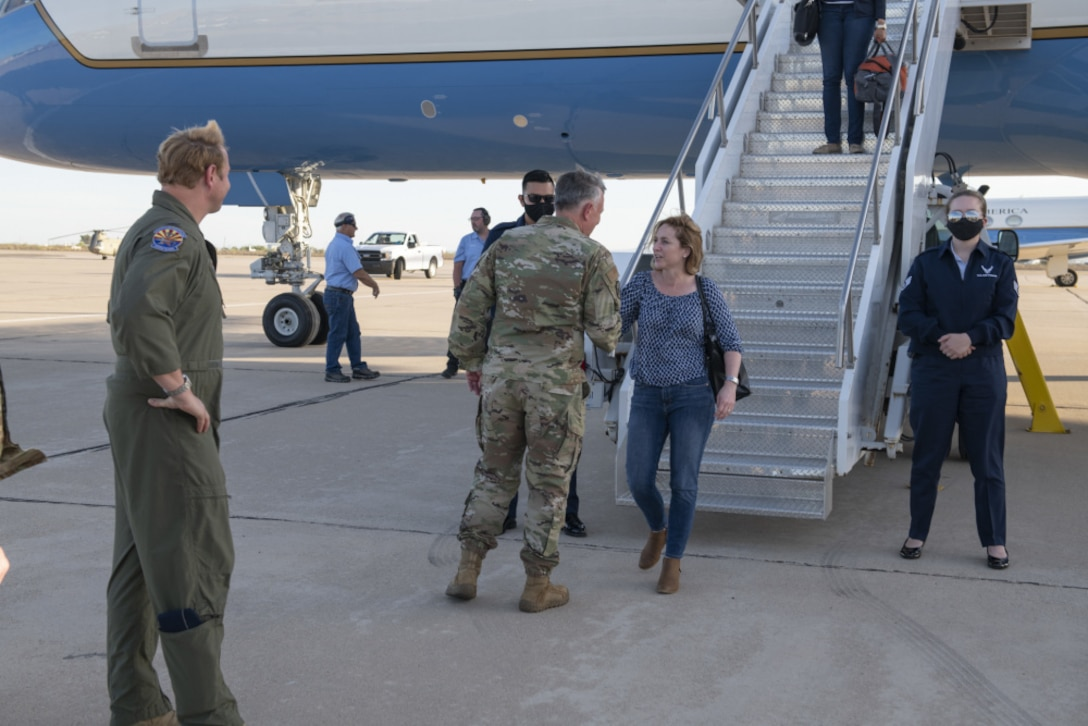 On a tarmac, a man in a military uniform shakes the hand of a woman who has descended the steps of an airplane.