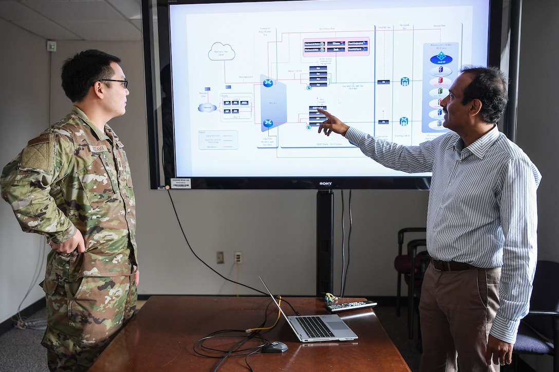 Capt. Christopher Kodama, branch engineer, and Raju Ranjan, an engineer from the AFNet Sustainment and Operations Branch discuss plans for a modern software-based perimeter at Hanscom Air Force Base, Mass., June 3, 2021. HNIB personnel are partnering with the Air Combat Command Directorate of Cyberspace and Information Dominance to develop the perimeter, which will deliver zero trust capability to applications across the Air Force.