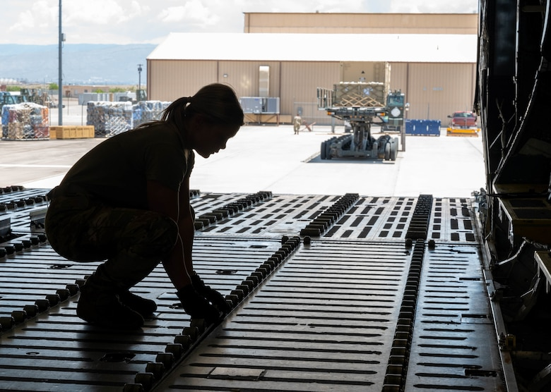 Airman 1st Class Rebecca Reimer, 9th Airlift Squadron loadmaster student, secures rollers to the cargo deck of a Dover Air Force Base C-5M Super Galaxy during a Major Command Service Tail Trainer exercise at Holloman AFB, New Mexico, June 2, 2021. The 9th AS performs MSTTs to expedite upgrade and qualification training for C-5M loadmasters and flight engineers. Over the course of the 10-day MSTT, 9th AS loadmasters loaded and unloaded 320,085 pounds of cargo, including palletized cargo, aircraft ground equipment, a fuel truck and a K-loader. (U.S. Air Force photo by Senior Airman Faith Schaefer)