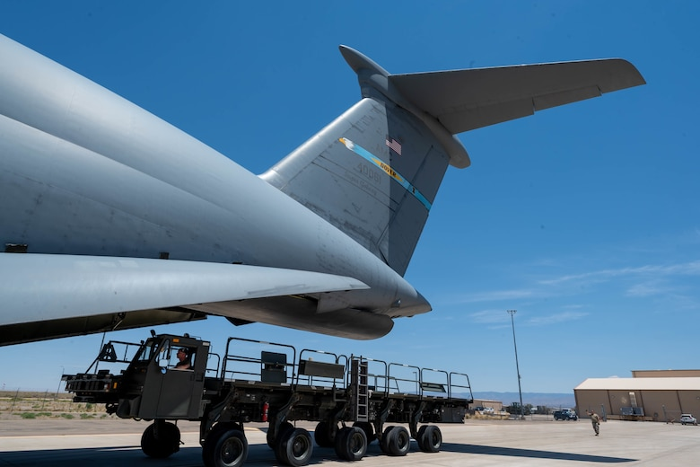 A K-loader is loaded onto a Dover Air Force Base C-5M Super Galaxy during a Major Command Service Tail Trainer at Holloman AFB, New Mexico, June 9, 2021. Loadmasters from the 9th Airlift Squadron coordinated cargo with Airmen from the 49th Wing and 635th Materiel Maintenance Group to complete the 10-day MSTT. Over the course of the training, Airmen loaded and unloaded 320,085 pounds of cargo, including palletized cargo, aircraft ground equipment, a fuel truck and a K-loader. (U.S. Air Force photo by Senior Airman Faith Schaefer)