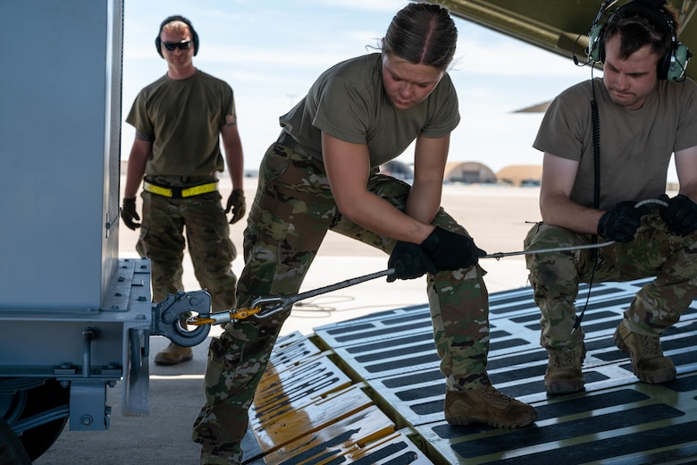Airman 1st Class Rebecca Reimer, center, 9th Airlift Squadron student loadmaster, and Staff Sgt. John Dittess, right, 9th AS loadmaster, attach a winch to aircraft ground equipment before loading it onto a Dover Air Force Base C-5M Super Galaxy during a Major Command Service Tail Trainer, at Holloman AFB, June 8, 2021. Loadmasters from the 9th AS coordinated cargo with Airmen from Air Education and Training Command's 49th Wing and Air Force Materiel Command's 635th Materiel Maintenance Group to complete the 10-day MSTT. Over the course of the training, Airmen loaded and unloaded 320,085 pounds of cargo, including palletized cargo, AGE, a fuel truck and a K-loader. (U.S. Air Force photo by Senior Airman Faith Schaefer)