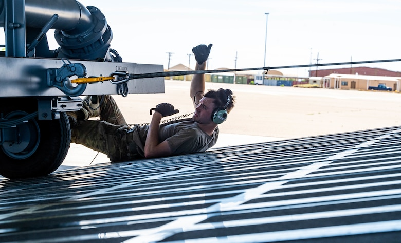 Staff Sgt. John Dittess, 9th Airlift Squadron loadmaster, assists in marshaling aircraft ground equipment onto a Dover Air Force Base C-5M Super Galaxy during a Major Command Service Tail Trainer, at Holloman AFB, June 8, 2021. Loadmasters from the 9th AS coordinated cargo with Airmen from Air Education and Training Command's 49th Wing and Air Force Materiel Command's 635th Material Maintenance Group to complete the 10-day MSTT. Over the course of the training, Airmen loaded and unloaded 320,085 pounds of cargo, including palletized cargo, AGE, a fuel truck and a K-loader. (U.S. Air Force photo by Senior Airman Faith Schaefer)