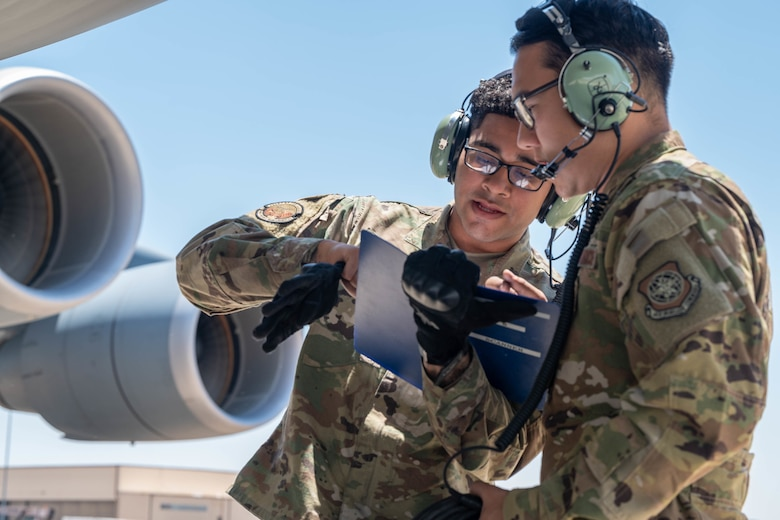 Senior Airman Edwin Vado, left, 436th Aircraft Maintenance Squadron flying crew chief, and Staff Sgt. Alex Delamarter, 9th Airlift Squadron student flight engineer, review an Engines Running Onload checklist for a Dover Air Force Base C-5M Super Galaxy during a Major Command Service Tail Trainer at Holloman AFB, New Mexico, June 7, 2021. The 9th AS performs MSTTs to expedite upgrade and qualification training for C-5M loadmasters and flight engineers.(U.S. Air Force photo by Senior Airman Faith Schaefer)