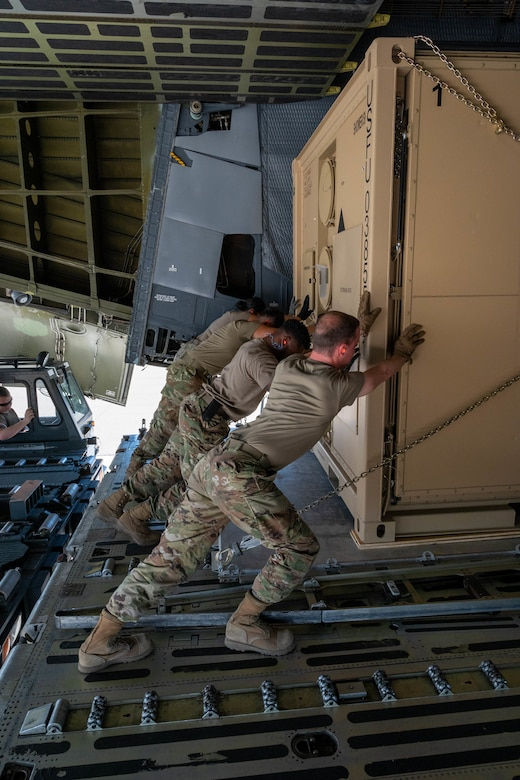 Airmen from the 635th Materiel Maintenance Group push palletized cargo onto a Dover Air Force Base C-5M Super Galaxy during a Major Command Service Tail Trainer exercise at Holloman AFB, New Mexico, June 2, 2021. Loadmasters from the 9th Airlift Squadron coordinated cargo with Air Education and Training Command's 49th Wing and Air Force Materiel Command's 635th MMG Airmen to complete the 10-day MSTT. During the training, Airmen loaded and unloaded 320,085 pounds of cargo, including palletized cargo, aircraft ground equipment, a fuel truck and a K-loader. (U.S. Air Force photo by Senior Airman Faith Schaefer)