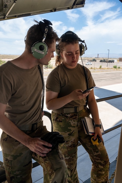 Staff Sgt. John Dittess, left, and Senior Airman Amelia Bradfield, both 9th Airlift Squadron loadmasters, calculate the weight of palletized cargo before loading it onto a Dover Air Force Base C-5M Super Galaxy during a Major Command Service Tail Trainer exercise at Holloman AFB, New Mexico, June 2, 2021.The 9th AS performs MSTTs to expedite upgrade and qualification training for C-5M loadmasters and flight engineers. Over the course of the 10-day MSTT, 9th AS loadmasters loaded and unloaded 320,085 pounds of cargo, including palletized cargo, aircraft ground equipment, a fuel truck and a K-loader. (U.S. Air Force photo by Senior Airman Faith Schaefer)