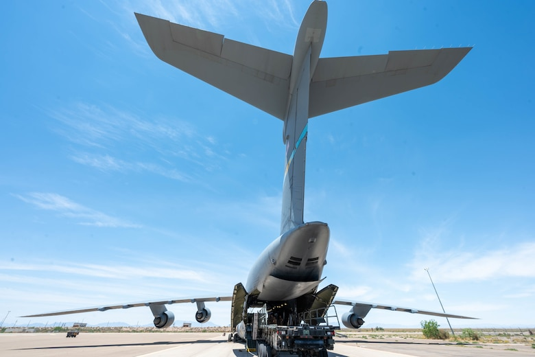 Airmen from the 49th Logistics Readiness Squadron load a K-loader onto a Dover Air Force Base C-5M Super Galaxy during a Major Command Service Tail Trainer exercise at Holloman AFB, New Mexico, June 9, 2021. During the training exercise, Airmen loaded and unloaded 320,085 pounds of cargo, including palletized cargo, aircraft ground equipment, a fuel truck and a K-loader. (U.S. Air Force photo by Senior Airman Faith Schaefer)