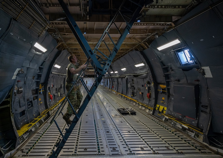 Staff Sgt. Justin Thomas, 9th Airlift Squadron noncommissioned officer in charge of loadmaster training, climbs the troop deck stairs of a Dover Air Force Base C-5M Super Galaxy during a Major Command Service Tail Trainer at Holloman AFB, New Mexico, June 4, 2021. The 9th AS performs MSTTs to expedite upgrade and qualification training for C-5M loadmasters and flight engineers. Of the 350 tasks needed to be a fully qualified loadmaster, roughly half can be completed during an MSTT, reducing the time of training by up to 35 days. (U.S. Air Force photo by Senior Airman Faith Schaefer)