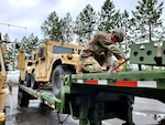 A Washington National Guard member of the 1041st Transportation Company ensures equipment is tied down before departing Fairchild Air Force Base, Wash., June 7, 2021, for annual training at Fort Harrison, Montana.