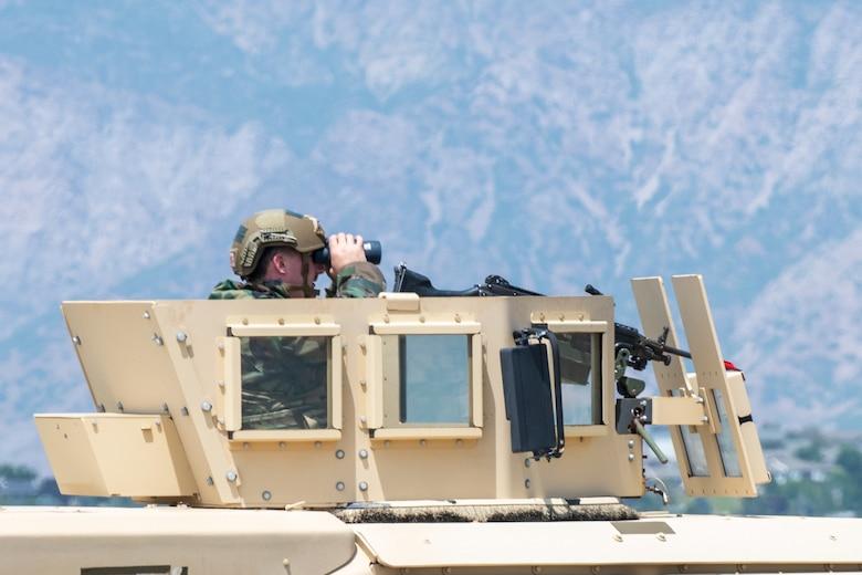 An Airmen inside the turret on a Humvee looking through binoculars.