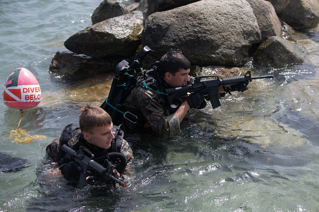 U.S. Marine Corps Cpl. David Ballek, a native of Bemidji, Mass., left, and Cpl. Jonathan Derisio, a native of Portland, Ore., both reconnaissance Marines with 2d Reconnaissance Battalion (2d Recon), 2d Marine Division, emerge from the water after a team dive during Exercise Caribbean Coastal Warrior on Savaneta Kamp, Aruba, June 12, 2021. The exercise allows 2d Recon to expand its knowledge and proficiency when operating in littoral and coastal regions while increasing global interoperability with 32nd Raiding Squadron, Netherlands Marine Corps. (U.S. Marine Corps Lance Cpl. Jennifer E. Reyes)