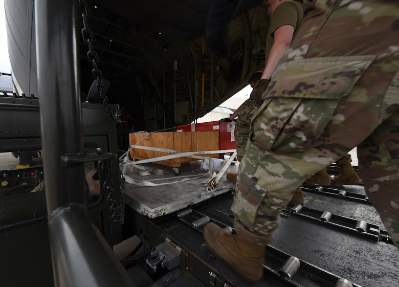 Members of the 721st Aerial Port Squadron special handling flight load supplies on to a C-130J Super Hercules aircraft at Ramstein Air Base, Germany, June 18, 2021. The 721st APS special handlers manage cargo ranging from medical supplies to dignified transfers. (U.S. Air Force photo by Senior Airman Thomas Karol)
