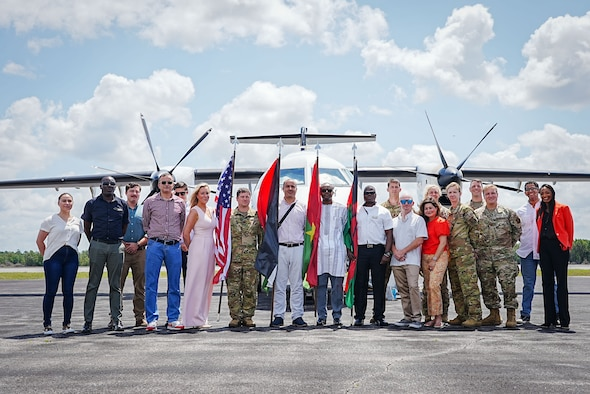 Group of Airmen, civilians and students pose for a photo in front of an aircraft while holding flags.