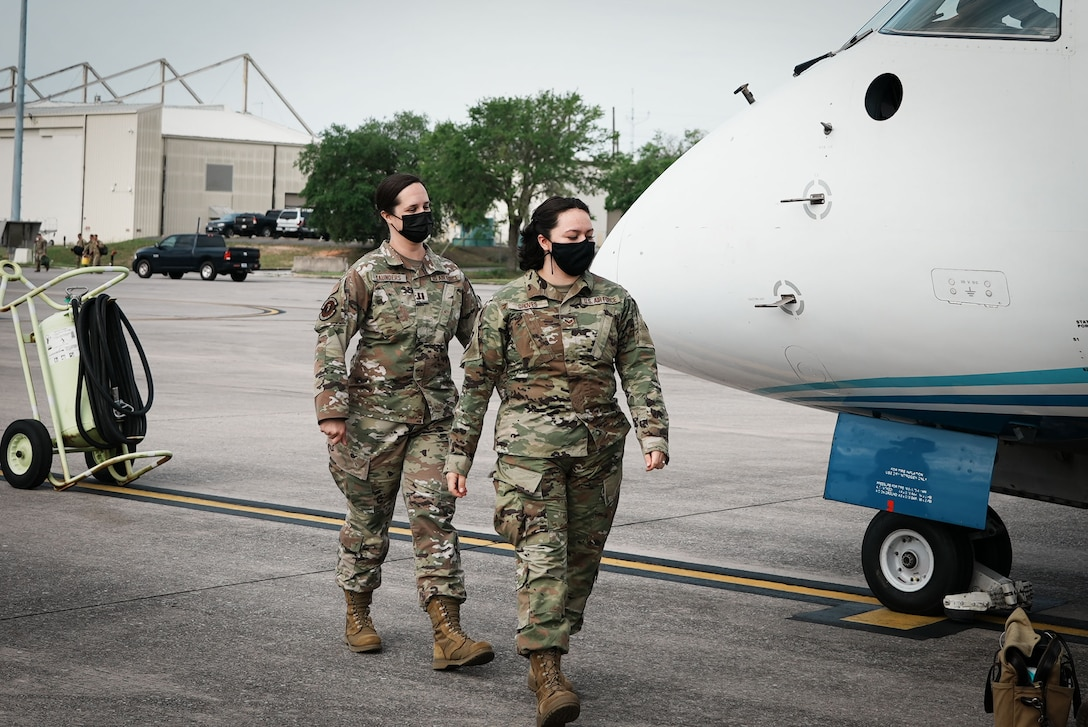 Two Airmen prepare to board a C-146A Wolfhound aircraft.