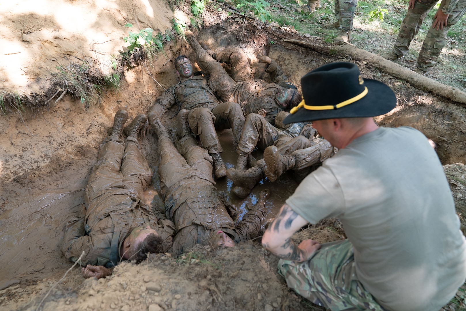 After crawling through a muddy trench, Soldiers in the Wisconsin Army National Guard's 1st Squadron, 105th Cavalry, are quizzed on cavalry knowledge as part of a voluntary qualification course known as a spur ride June 15, 2021, at Fort McCoy. Cavalry troopers who successfully complete the ride earn their spurs.