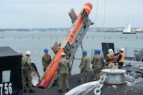 SAN DIEGO (June 22, 2021) Sailors load an inert encapsulated harpoon onto the the Los Angeles-class fast-attack submarine USS Scranton (SSN 756) The harpoon system provides commanders with lethal all-weather anti-ship capability to rapidly engage targets at long range. (U.S. Navy Photo by Mass Communication Specialist 2nd Class Thomas Gooley/Released)