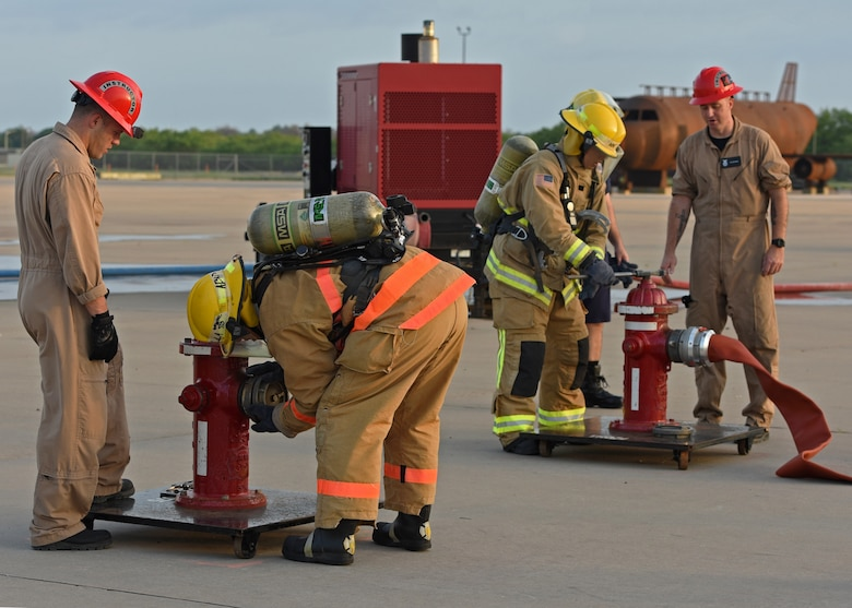 Joint service fire protection students from the 312th Training Squadron attach hoses to fire hydrants during their training on Goodfellow Air Force Base, Texas, June 11, 2021. Students were timed on how quickly they could carry the 200 foot fire hose and attach it to the fire hydrant. (U.S. Air Force photo by Senior Airman Abbey Rieves)