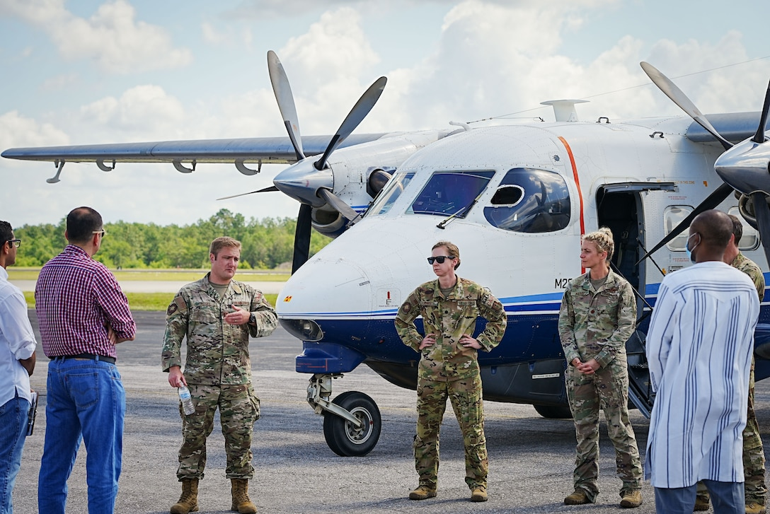 Airmen speak to students in front of aircraft