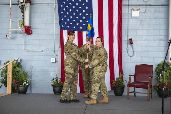 A woman in a air force uniform passes a guidon to another woman in a air force uniform.