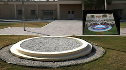The former headquarters building of Area Support Group-Qatar at the now-closed Camp As Sayliyah-Main, Qatar, is seen here in this June 14, 2021 photograph without the large representation of the U.S. Army Central shoulder patch in front of the buildings with the flag pole. ASG-Qatar cased its colors at a June 10, 2021 ceremony that marked the closing of installation first established in 1992. The inset photograph shows the Boy Scouts, their leaders and others with American School of Doha Service Troop 970 during their 2013 camporee hosted at CAS-Main.
