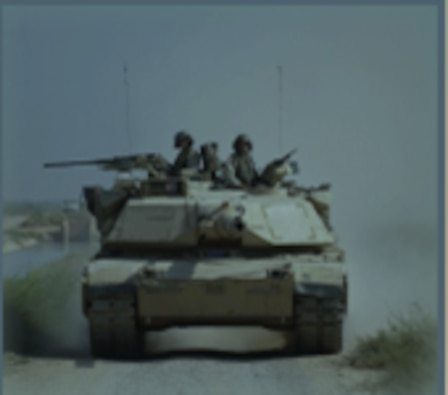 A front angle view of the M1 Abrams Tank rolling toward the camera on a dirt road with two service members sitting on top.