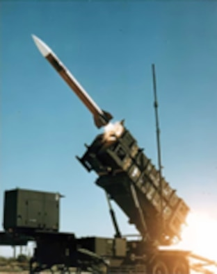 A side view of the Patriot missile atop a mobile unit, with the missile loaded and pointing at a 45 degree angle toward the sky.