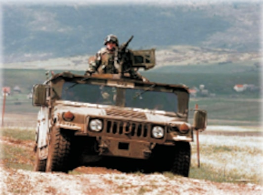The HMMWV from the front angle, rolling across a rocky mountainous setting.