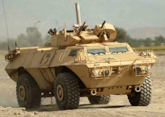 The ASV, a 4-wheeled armored vehicle from a front angle, rollilng toward the camera in a desert setting.