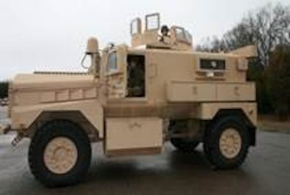 Side angle view of the IOM Cougar, a four wheel armored vehicle sitting atop a blacktop road with trees in the background.