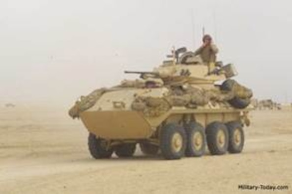 Eight-wheeled KMA Stryker vehicle rolling toward the camera in a desert setting with a service member sitting on top.