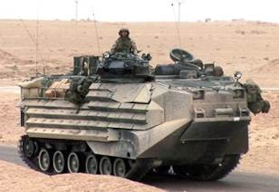 Light Armored Vehicle rolling down a paved road with a service member sitting on top.